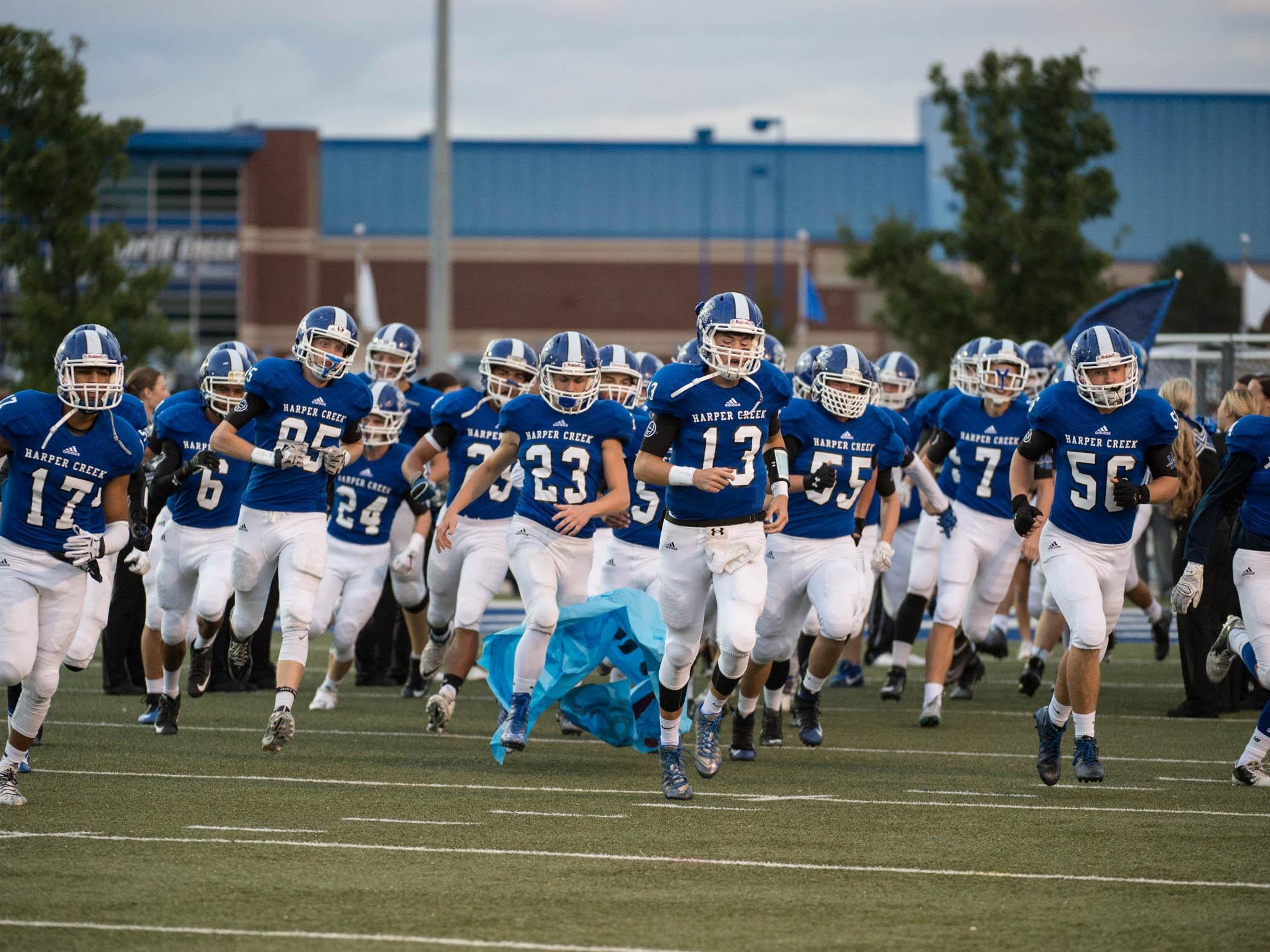 Harper Creek players take the field Friday evening against Coldwater.