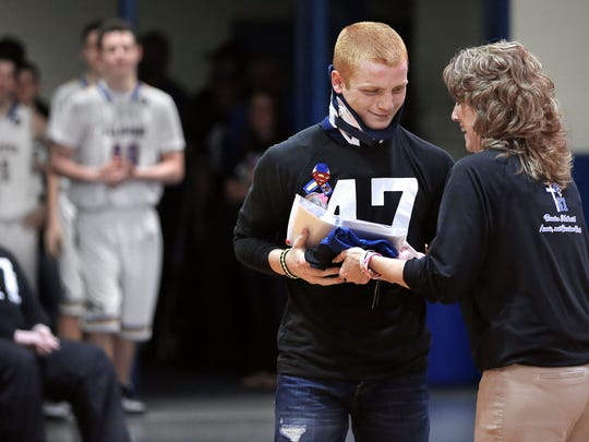 North Vermillion Principal Jayne Virostko hands their IHSAA State Championship football ring to player Ethan Lee during a ceremony held at the school on Saturday, Feb. 7, 2015.