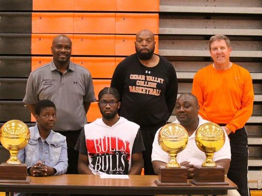 Burkburnett senior Shonne Carter (seated center) signed to play basketball at Cedar Valley College this week.
