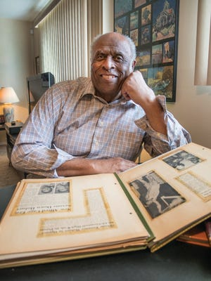 Warren Sutton reminisces while looking through one of his many scrapbooks. Sutton will receive an honorary degree from Alfred University on Saturday.