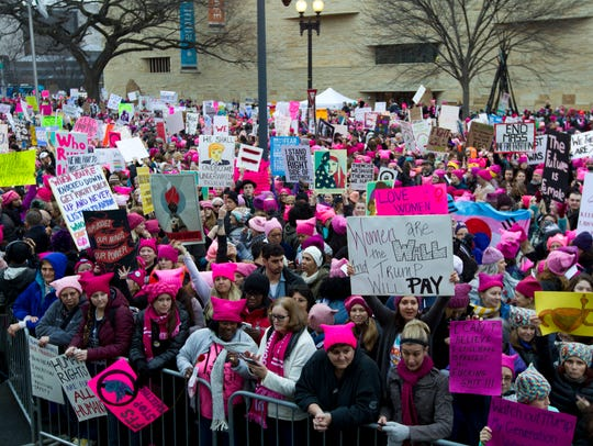 Women with bright pink hats and signs begin to gather