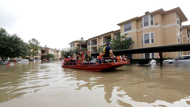 In this April 19 photo, residents are evacuated from their flooded apartment complex in Houston. Storms dumped more than a foot of rain in the Houston area, flooding dozens of neighborhoods.