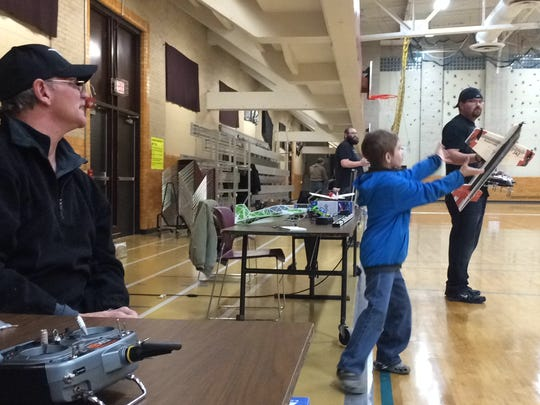Geoff Stoner of Wisconsin Rapids watches as his grandson attempts to catch a radio-controlled airplane — as a larger plane looms close by — during a recent Friday night River Valley Flyers flight session at East Junior High School.