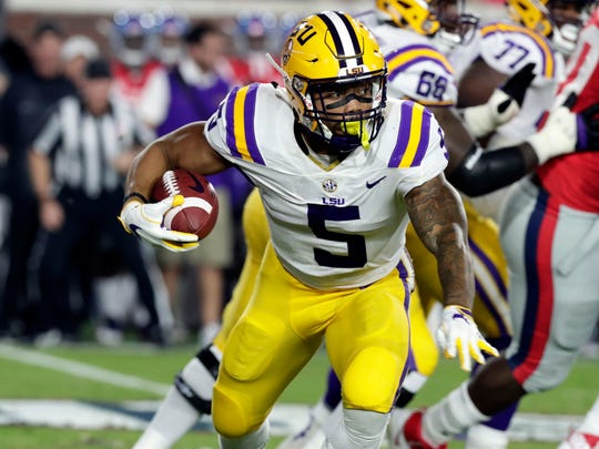 LSU running back Derrius Guice (5) runs for a first down past Mississippi defenders in the first half of an NCAA college football game in Oxford, Miss., Saturday, Oct. 21, 2017.