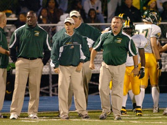A group of Indian River coaches shout directions during a high school football game in 2009. As part of cuts being considered by the district, the amount of paid coaching staff for athletics would be reduced.