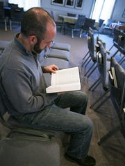 Matthew Bucher, pastor at Immanuel Mennonite Church in Harrisonburg, reads a verse from the Bible at his church on Feb. 2, 2017. Bucher created the message that was the inspiration for the green, blue and orange welcome signs that now are in yards across the country.