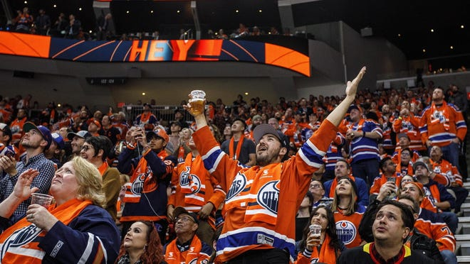 FILE - In this Oct. 2, 2019, file photo, Edmonton Oilers fans celebrate a goal against the Vancouver Canucks during the first period of an NHL hockey game in Edmonton, Alberta.