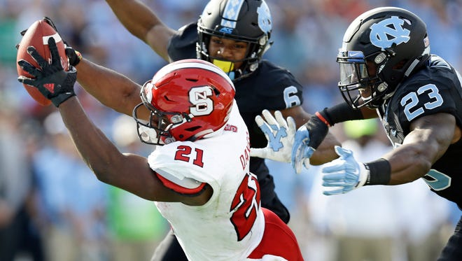 North Carolina State's Matthew Dayes (21) reaches out out for a touchdown as North Carolina's M.J. Stewart (6) and Cayson Collins (23) try to tackle during the first half of an NCAA college football game in Chapel Hill on Friday, Nov. 25, 2016.