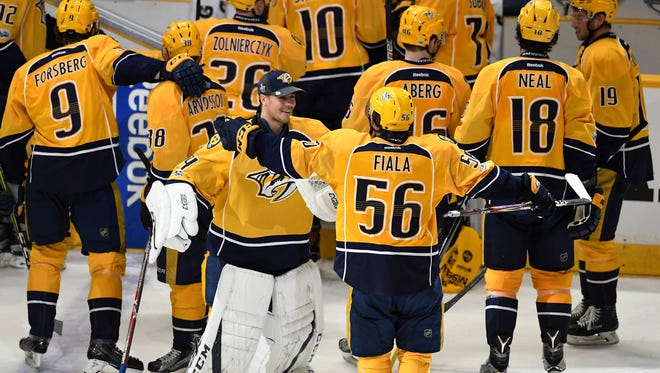 Nashville Predators left wing Kevin Fiala (56) celebrates with goalie Juuse Saros (74) and his teammates after his goal won game three in the first-round NHL playoff series at the Bridgestone Arena, Tuesday, April 18, 2017, in Nashville, Tenn.