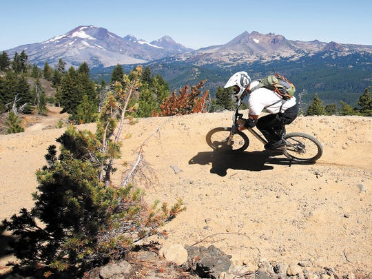 In this Sept. 4, 2013 photo, Tom Lomax rides around one of the wide banked turns on the Lava Flow Trail at the new Mount Bachelor downhill bike park in Bend.