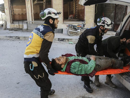 This photo released Feb. 19, 2019, by the Syrian Civil Defense group known as the White Helmets, shows Syrian White Helmet civil defense workers carrying an injured man who was wounded by a shell from Syrian forces, in the town of Khan Sheikhoun, Idlib, north Syria.