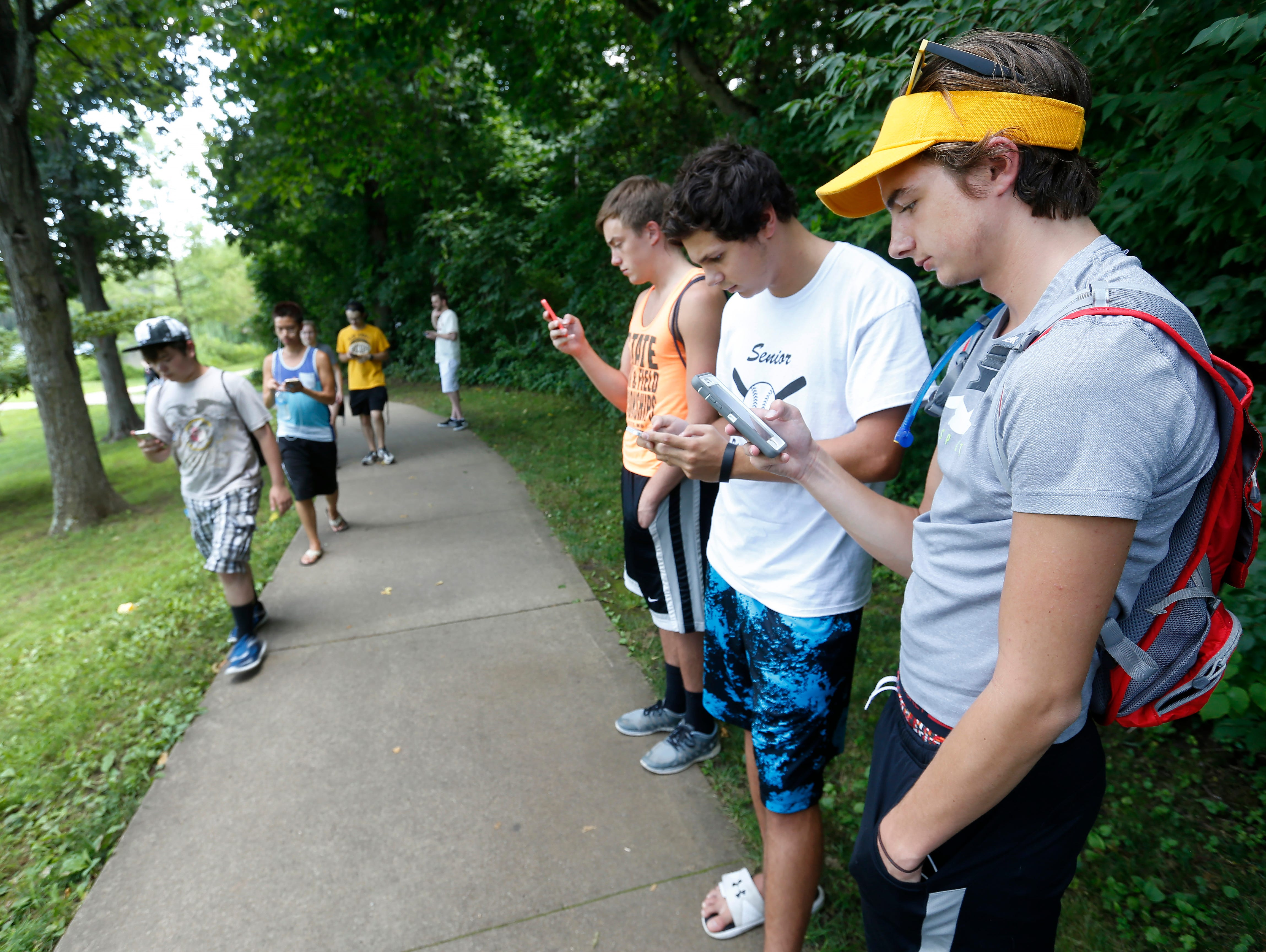 From right, Mitch Johnson, Kyle Cavanaugh and Logan Beach, all of Springfield, play Pokemon GO on their cell phones at Nathanael Greene Park on Monday, July 11, 2016.