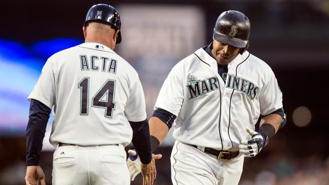 Seattle Mariners' Nelson Cruz, right, is congratulated by third base coach Manny Acta after hitting a solo home run off Los Angeles Angels starting pitcher Tyler Skaggs during the fourth inning of a baseball game, Saturday, Sept. 3, 2016, in Seattle.