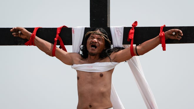 Filipino penitent Ruben Enaje reacts as he is nailed to a wooden cross for the 32nd year on Good Friday in San Pedro Cutud village, San Fernando, Pampanga, north of Manila, Philippines, on March 30, 2018.