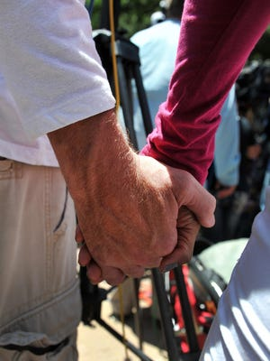 A couple hold  hands during a July 8, 2016, prayer event held in Dallas for  police officers who were killed and wounded during a mass shooting the night before. Dallas leaders encouraged everyone to hold hands during the event.