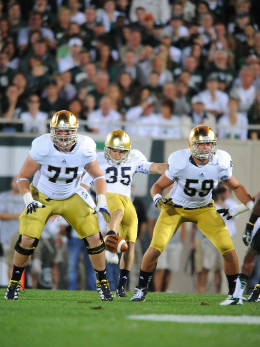 Notre Dame's Matt Hegarty (77) plays on the punt protection unit alongside Jarrett Grace (59) as Ben Turk punts the ball during a game at Michigan State on Sept. 15, 2012 in East Lansing, Mich.