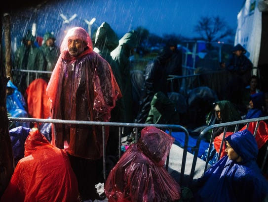 Refugees and migrants sit under the rain near the gate