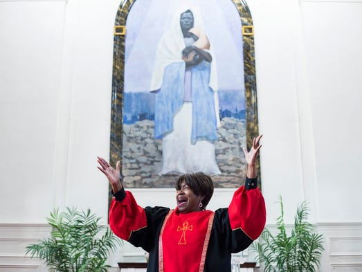 Oyin Mason, 64, leads the congregation in song during