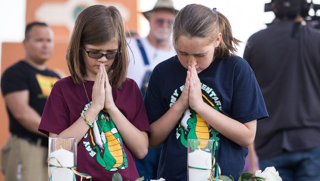 Two young girls say a prayer over bibles and candles places out Friday evening during a vigil at Texas First Bank in Santa Fe Texas for the victims of the shooting at Santa Fe High School that left 10 dead Friday, May 18, 2018.
