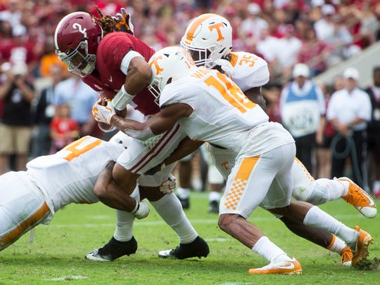 Tennessee defenders take down Alabama quarterback Jalen Hurts (2) in a game in 2017.