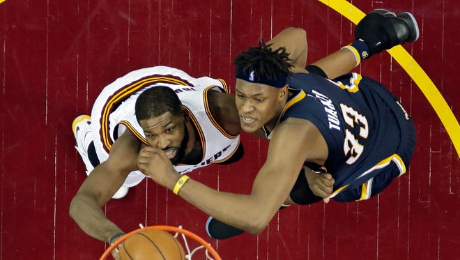 Cleveland Cavaliers' Tristan Thompson, left, drives to the basket against Indiana Pacers' Myles Turner in the first half in Game 2 of a first-round NBA basketball playoff series, Monday, April 17, 2017, in Cleveland. The Cavaliers won 117-111. (AP Photo/Tony Dejak)