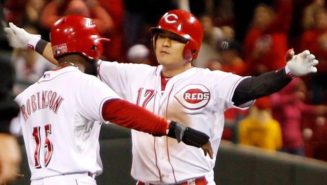 Cincinnati Reds center fielder Shin-Soo Choo is congratulated by left fielder Derrick Robinson  after hitting the game-winning single during the tenth inning.