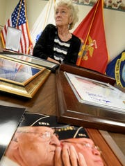 Polly Russo listens to the accomplishments of her late husband Frank Russo on Wednesday morning amidst photos, awards and honors he had attained over the years for his service.