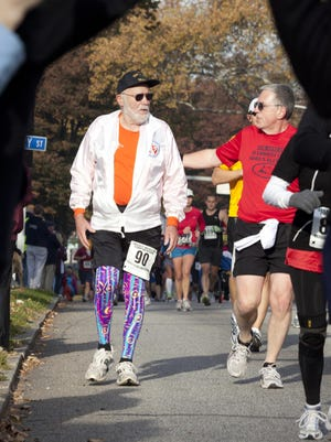 Don McNelly, left, receives encouragement from an unidentified runner during  the 2010 Harrisburg Marathon in Harrisburg, Pennsylvania.