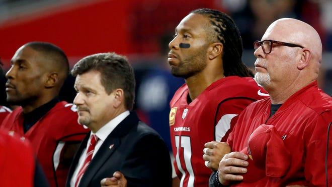 From left; Arizona Cardinals cornerback Patrick Peterson, president Michael Bidwill, wide receiver Larry Fitzgerald and head coach Bruce Arians stand during the national anthem prior to an NFL football game against the Dallas Cowboys, Monday, Sept. 25, 2017, in Glendale, Ariz.