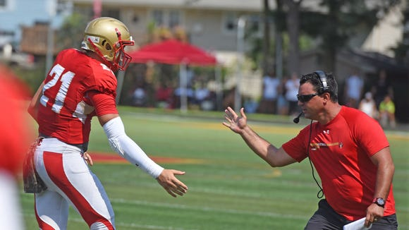 Nunzio Campanile high-fives Bergen Catholic quarterback Johnny Langan after a touchdown pass during a 2016 scrimmage.