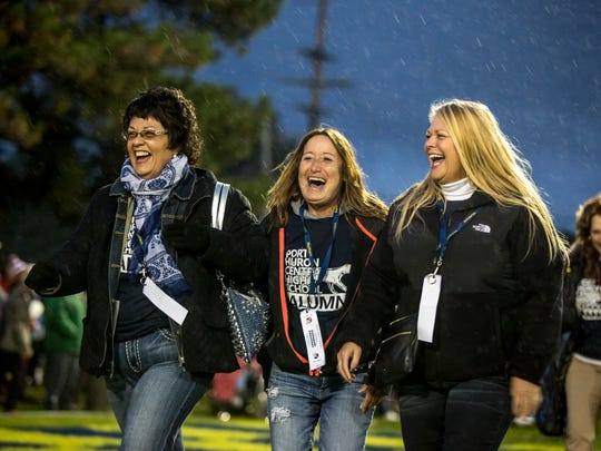 Port Huron Central High School class of 1979 members Kim Fischer Hudy, Dianna Pickelhaupt Wilson, and Holly Goodrich walk across the field as they are recognized during the Crosstown Showdown Friday, Oct. 21, 2016 at Memorial Stadium in Port Huron.
