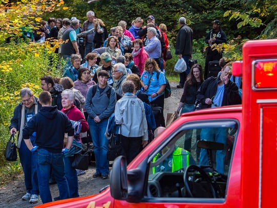 Passengers evacuated from a derailed Amtrak train wait to board school buses near Bull Run Road in Northfield on Monday, October 5, 2015.