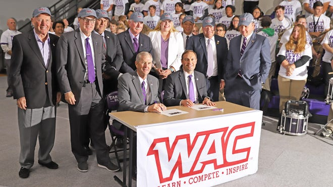 Western Athletic Conference Commissioner Jeff Hurd (seated, left) and Tarleton State University President Dr. James Hurley, backed by representatives from the Texas A&M University system and other officials are pictured during the signing of the agreement to join the WAC last November.