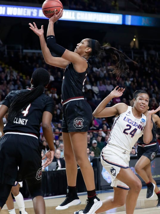 South Carolina's A'ja Wilson, center, drives past Connecticut's Napheesa Collier (24) during the first half of a regional final at the a women's NCAA college basketball tournament Monday, March 26, 2018, in Albany, N.Y. (AP Photo/Frank Franklin II)