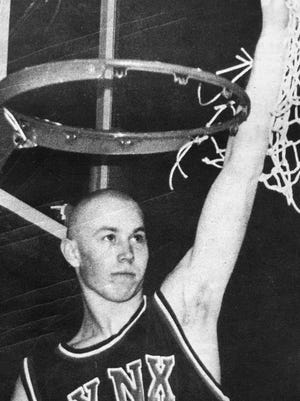 Austin Hansen of Brandon Valley raises the net after cutting it down at the Rushmore Plaza Civic Center after winning the Class AA state championship 20 years ago.