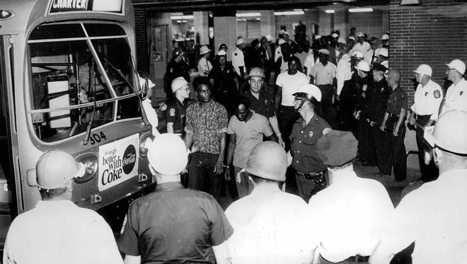 Under heavy guard, prisoners arrested during the riot are taken by bus to county jail. (