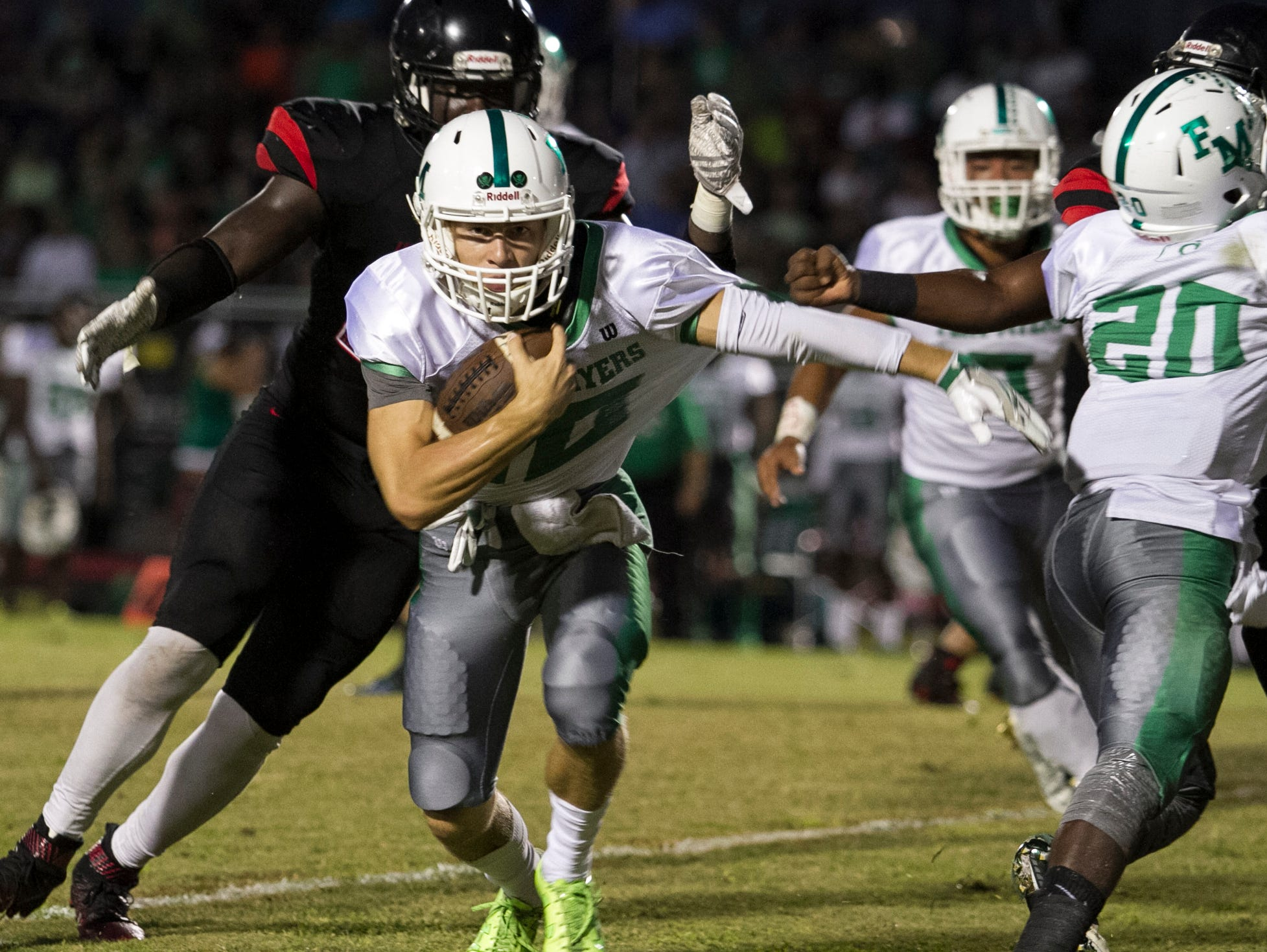 Fort Myers High School's Benjamin Stobough gets pulled down by a Wolfpack defender during a first half positive yardage run Friday avening.