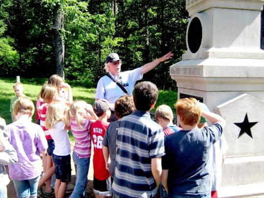 A licensed guide discusses a battlefield monument with a group of students visiting the Gettysburg National Military Park. If a partial government shutdown occurs Oct. 1, operations at the park will be among the hardest hit in the region. People would not be permitted to stroll about the battlefield and there would be no park rangers available through the Museum & Visitor Center to answer questions, park officials said.