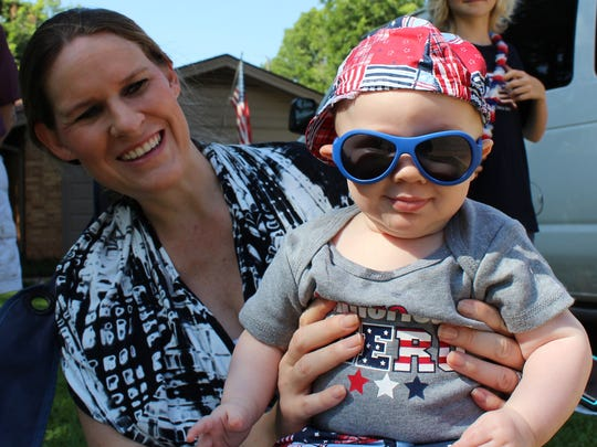 Mom Jordan Purifoy tries to coax a grin out of Phinneas, who's almost 5 months, at the River Oaks neighborhood parade.