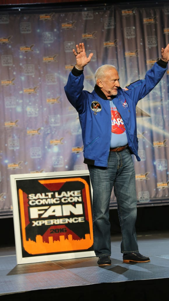 Apollo 11 astronaut Dr. Buzz Aldrin waves to a packed