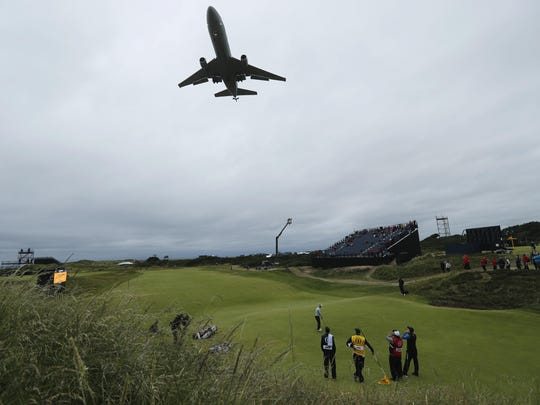 A group of players look up from the 8th green as a large plane comes into land at Prestwick Airport during the second round of the British Open Golf Championship at the Royal Troon Golf Club in Troon, Scotland, Friday, July 15, 2016. (AP Photo/Ben Curtis)