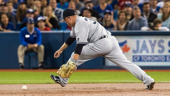 New York Yankees' Billy Butler chases the ball after committing an error against the Toronto Blue Jays during the first inning of a baseball game in Toronto, Friday, Sept. 23, 2016.
