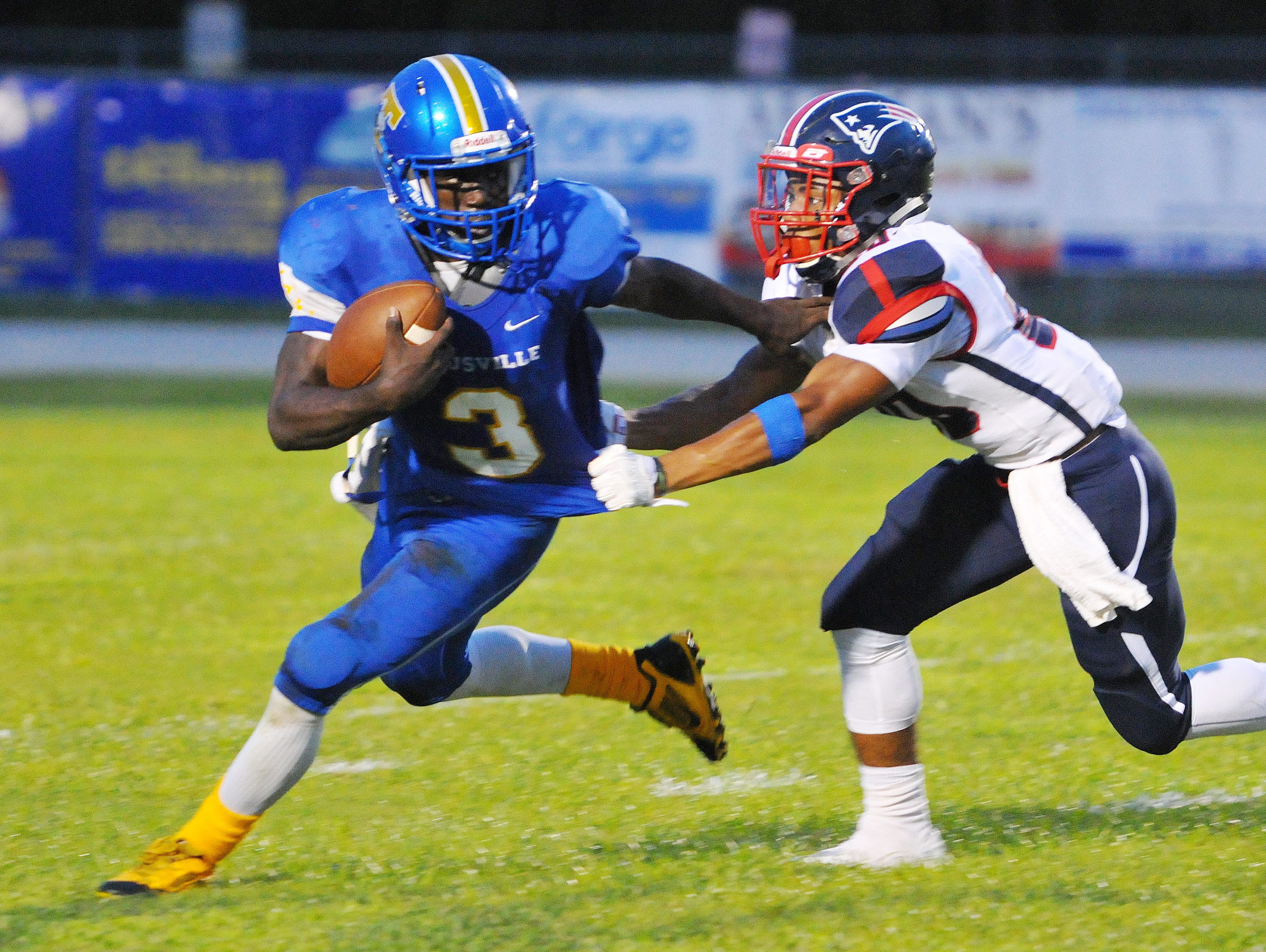 Titusville High's #3 Dontavious Marcus tries to escape the grasp of Lake Brantley High's #20 Paris Hennington during Friday nights game held at the Titusville High Stadium .