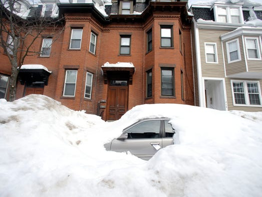 In this Feb. 23, 2015 file photo, a car remains buried