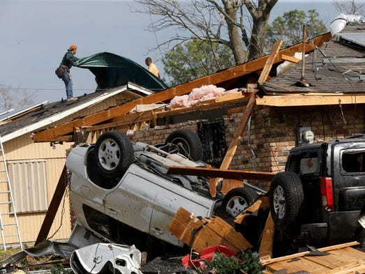 Workers put a tarp on the roof of a damaged home in
