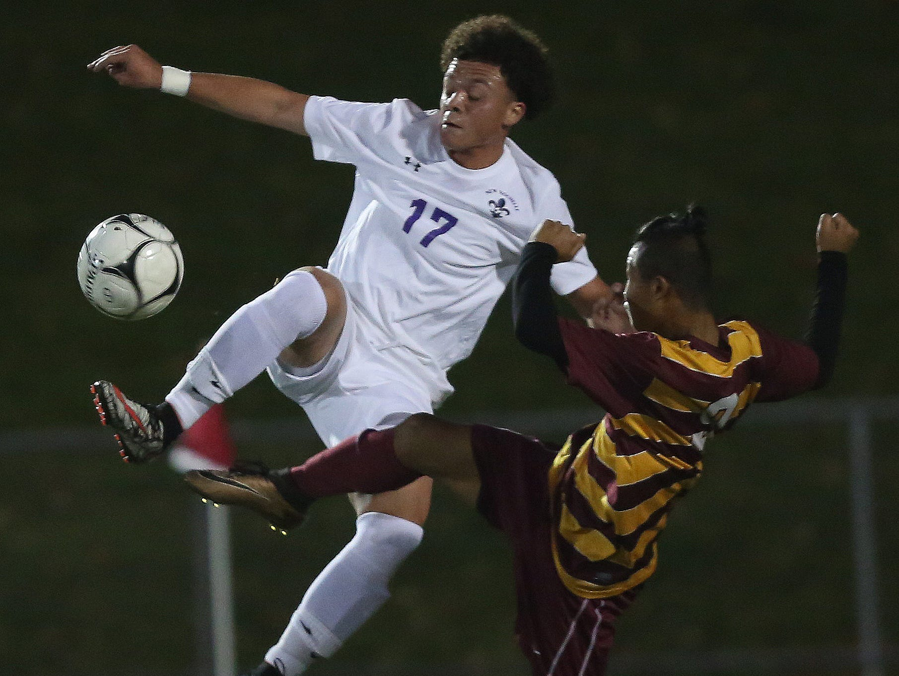 From left, New Rochelle's David Lopez (17) kicks the ball away from an Ithaca defender during the boys soccer regional semifinal at Lakeland High School in Shrub Oak Nov. 2, 2016.