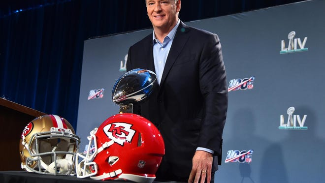 NFL commissioner Roger Goodell poses for a photo with the Vince Lombardi Trophy and helmets for the San Francisco 49ers and Kansas City Chiefs during a press conference before Super Bowl LIV at Hilton Downtown.
