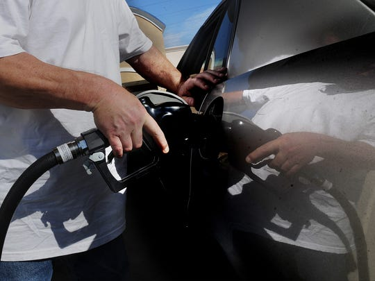 Ventura resident Randy Sartain puts gas into his vehicle. A 12-cents-per-gallon stategasoline excise tax went into effect Nov. 1 to raise moneyfor road and bridge repairs and public transit throughout California. The increase in prices has led some people to cut back on their holiday travel.