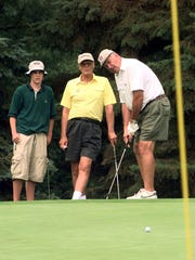 PLAYING FOR CHARITY:  John Martinkovic, right, putts
