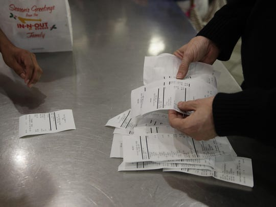 Father Jim Sichko counts receipts after buying lunch for customers at an In-N-Out Burger, in the Hollywood section of Los Angeles.